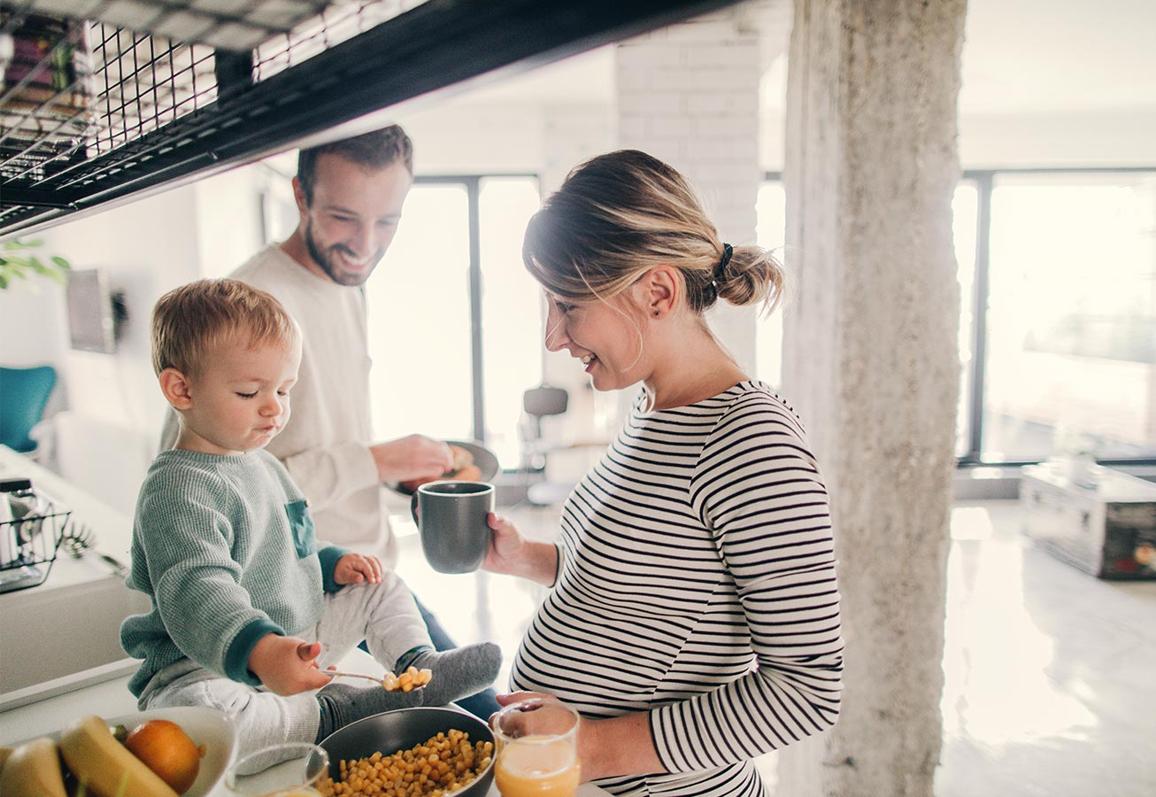 pregnant woman with son and husband cooking
